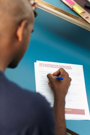 master degree: young adult african-american college student filling application form for master degree in library. Vertical shape, rear view, selective focus, head and shoulders