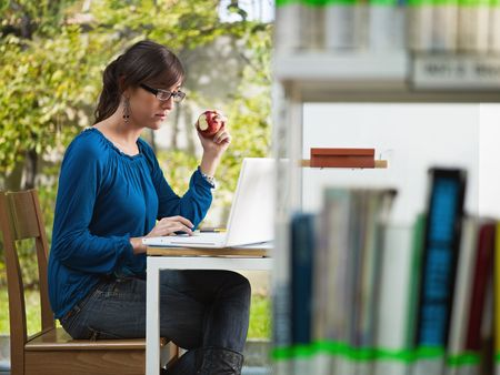 female college student studying in library and eating red apple. Horizontal shape, side view, three quarter length photo