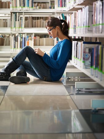koncentrace: female college student sitting on floor in library, reading book. Vertical shape, side view, full length, copy space Reklamní fotografie