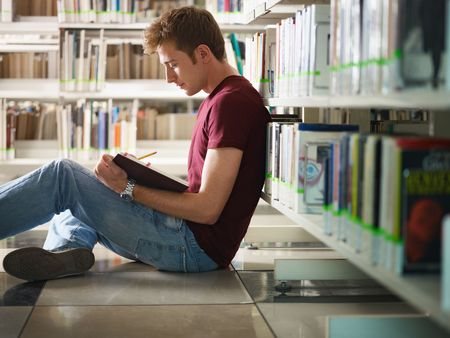 study: male college student sitting on floor in library, reading book. Horizontal shape, side view, three quarter length, copy space Stock Photo
