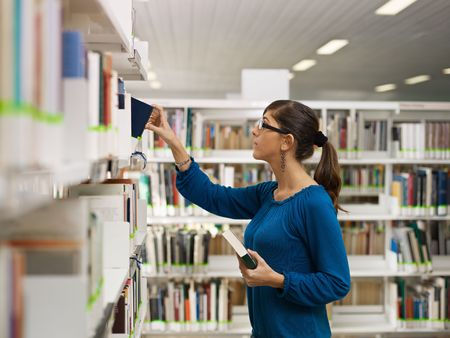 take away: female college student taking book from shelf in library. Horizontal shape, side view, waist up, copy space Stock Photo