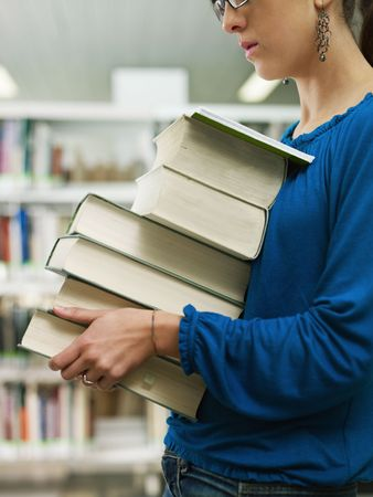 female college student carrying stack of books in library. Vertical shape, side view, mid section, copy space. Selective focus on face photo