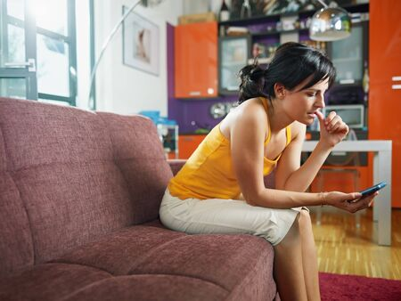 mordendo: mid adult woman on sofa staring at her mobile phone and biting nails. Horizontal shape, full length, copy space Imagens