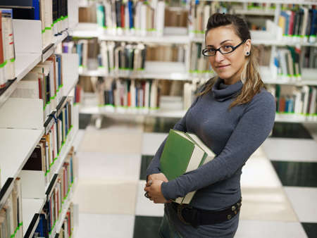 waist up: female college student with books standing near shelf in library. Horizontal shape, side view, waist up, copy space Stock Photo