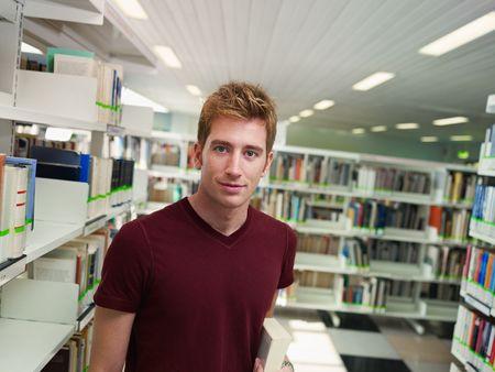 var�n: estudiante de colegio masculina con libro de pie cerca de estante de biblioteca. Forma horizontal, la vista frontal, la cintura para arriba, espacio de copia