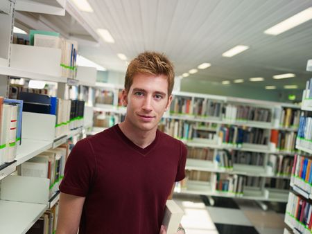 male college student with book standing near shelf in library. Horizontal shape, front view, waist up, copy space