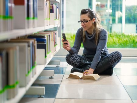 woman phone: female college student sitting on floor in library, typing on mobile phone. Horizontal shape, front view, full length, copy space