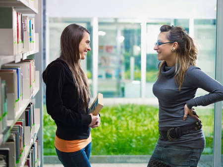 two female college students talking in library. Horizontal shape, side view, waist up photo
