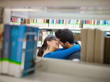 two caucasina students hugging and kissing behind shelves in library. Horizontal shape, side view, copy space photo