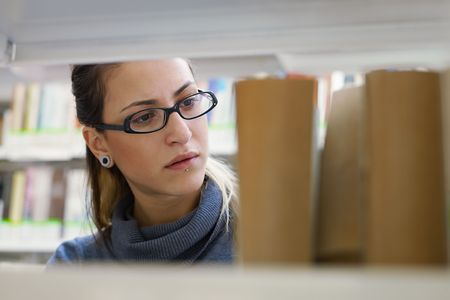 female college student taking book from shelf in library. Horizontal shape, front view, head and shoulders, copy space Stock Photo - 8113479