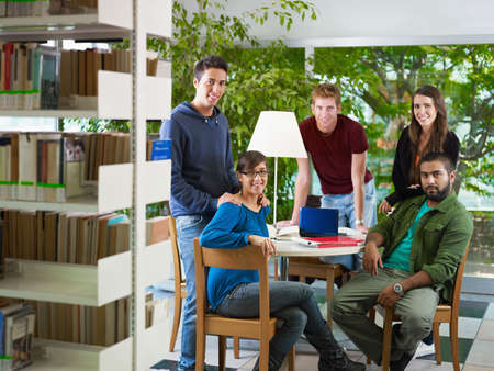 group of college students looking at camera in library. Horizontal shape, front view, full length photo
