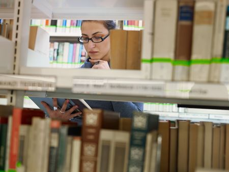 female college student reading book in library, behind shelf. Horizontal shape, front view, waist up, copy space photo