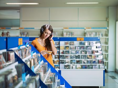 earphone: caucasian woman with headphones, choosing cd in music shop. Horizontal shape, front view, waist up, copy space