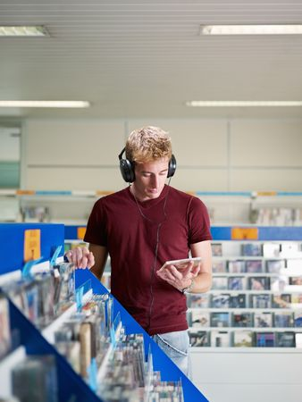 compact disk: caucasian man with headphones, choosing cd in music shop. Vertical shape, front view, waist up, copy space