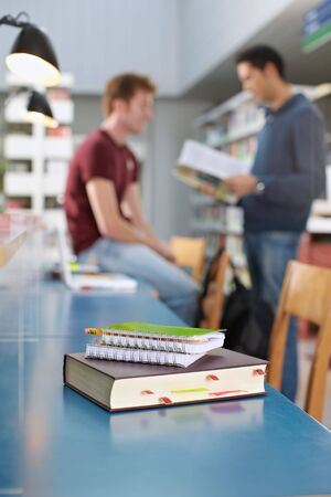 closeup of closed book on table. Two students talking in background. Vertical shape, copy space, focus on foreground photo