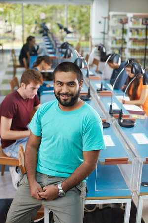 portrait of male college student sitting on table in library and looking at camera. Vertical shape, high angle view photo