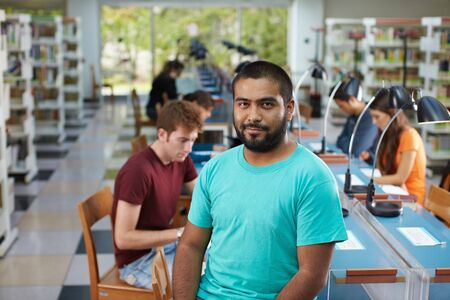portrait of male college student sitting on table in library and looking at camera. Horizontal shape, waist up photo