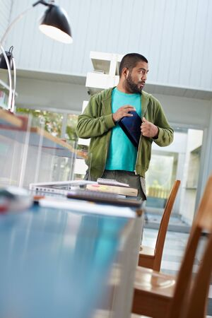 young adult man hiding laptop computer under jacket and looking away. Vertical shape, waist up, copy space photo