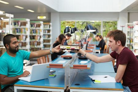 hispanic student: two college students sitting in library with laptop computer and sharing book. Horizontal shape, side view, copy space Stock Photo
