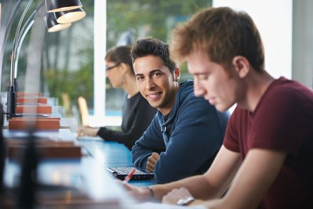 student reading: portrait of male college student sitting in library with laptop computer, looking at camera. Horizontal shape, side view, waist up Stock Photo