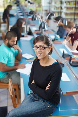 ハイアングルビュー: 女子短大生の図書館とカメラ目線でテーブルの上に座っての肖像画。ハイアングル垂直] 図形
