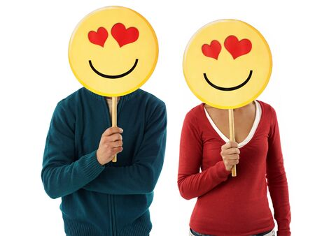happy emoticon: young adult woman and man holding emoticon with red hearts on white background. Horizontal shape, front view, waist up Stock Photo