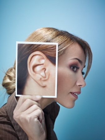 ears: mid adult business woman holding photo of her ear on blue background. Vertical shape, side view, head and shoulders, copy space