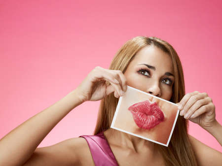 mid adult blond woman holding photo of her mouth kissing on pink background. Horizontal shape, front view, head and shoulders, copy space photo