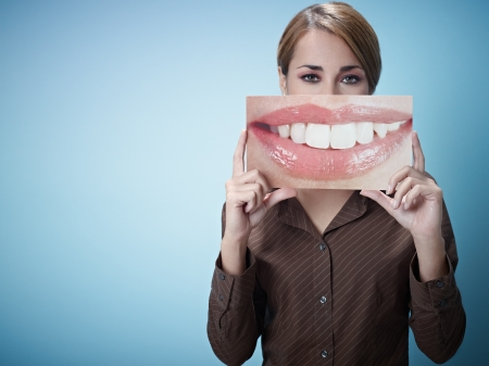 big mouth: mid adult business woman holding photo of toothy smile on blue background. Horizontal shape, front view, waist up, copy space