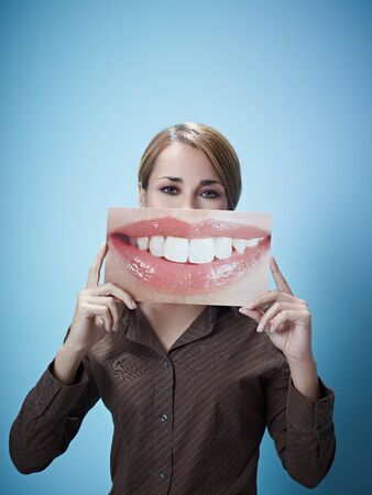 mid adult business woman holding photo of toothy smile on blue background. Vertical shape, front view, waist up, copy space photo