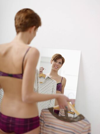 hair dressing: young adult caucasian female looking at mirror and choosing clothes. Vertical shape, waist up, copy space
