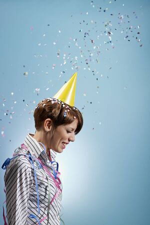 waist up: caucasian woman with confetti and streamers on shirt. Vertical shape, side view, waist up, copy space Stock Photo