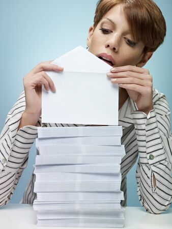caucasian secretary closing pile of envelopes. Vertical shape, front view, waist up, copy space photo