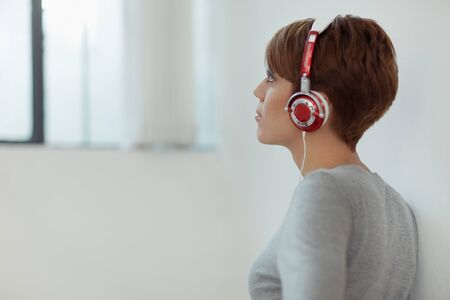 young adult caucasian woman with headphones at home. Horizontal shape, side view, copy space photo