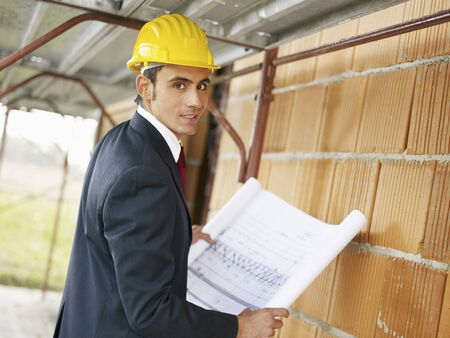 Architect holding blueprints and looking at camera. photo