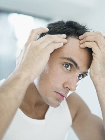 caucasian adult man checking hairline. Vertical shape, head and shoulders photo