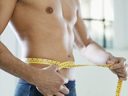 cintura perfecta: recorta la visi�n del hombre j�venes cauc�sicos, medir la cintura con cinta amarilla. Forma horizontal, a mediados de la secci�n, vista lateral Foto de archivo