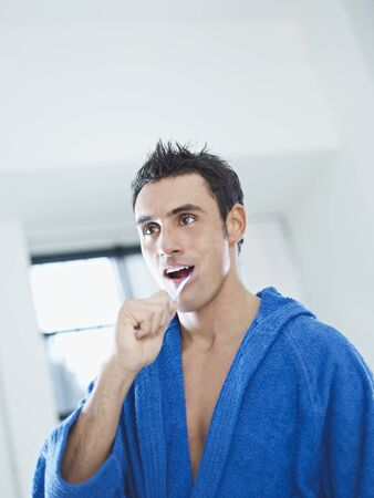 caucasian adult man with bathrobe brushing teeth in bathrooom. Vertical shape, waist up, copy space Stock Photo - 8440301