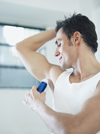 beautiful armpit: caucasian adult man applying stick deodorant. Vertical shape, waist up, copy space