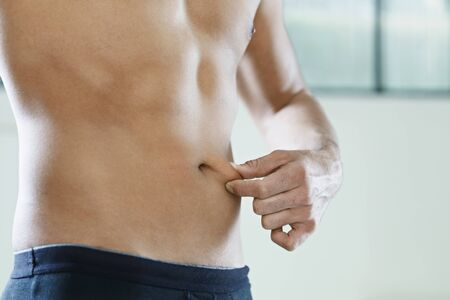 pinching: cropped view of young caucasian man measuring fat on belly. Horizontal shape, mid section, side view, copy space Stock Photo