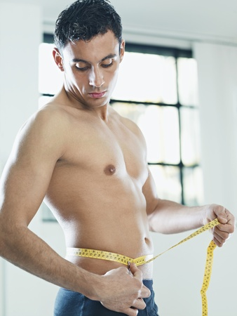 bare waist: caucasian young man measuring waist with yellow tape. Vertical shape, waist up, side view, copy space
