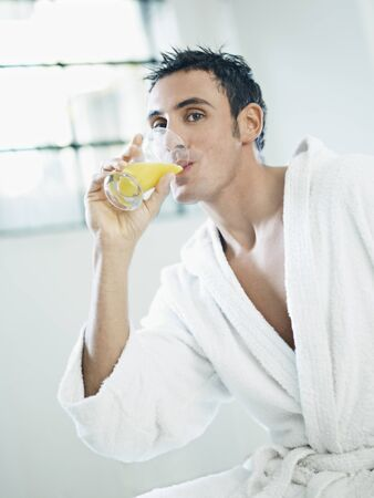 adult caucasian man in white bathrobe drinking orange juice. Vertical shape, waist up, side view Stock Photo - 8445829