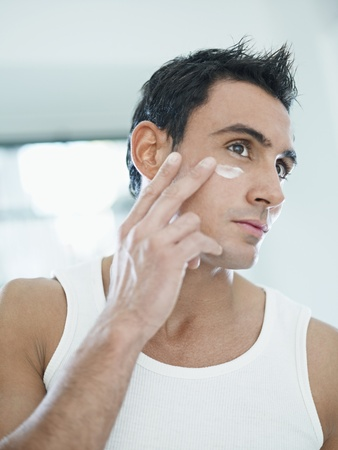 waist up: young caucasian man applying eye cream on face. Vertical shape, front view, waist up Stock Photo