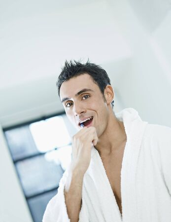 waist up: caucasian adult man with bathrobe brushing teeth in bathrooom and looking at camera. Vertical shape, waist up, copy space