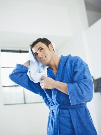 bathrobe: young caucasian man in blue bathrobe drying hair. Vertical shape, three quarter length, copy space