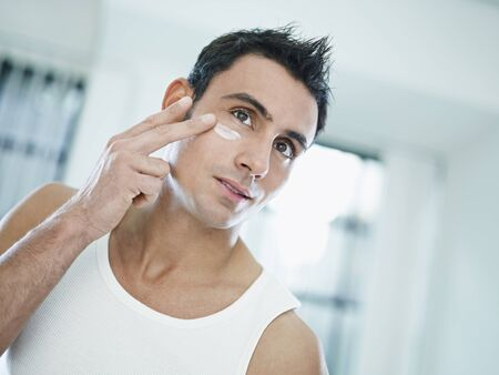 moisturizing: young caucasian man applying eye cream on face. Horizontal shape, front view, head and shoulders