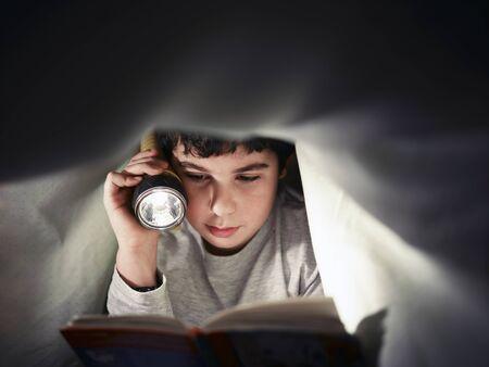 lezing: Caucasian kind lezen boek onder de dekens in de nacht. Vooraanzicht, kopieer ruimte