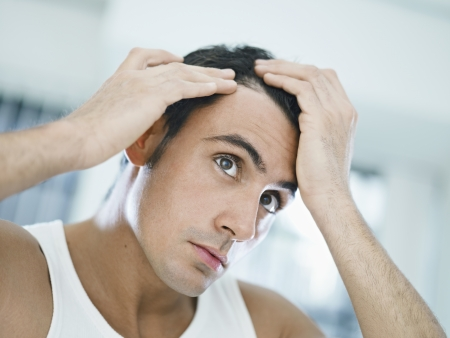concerns: caucasian adult man checking hairline. Horizontal shape, head and shoulders, front view
