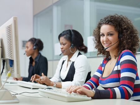 customer service representative: multiethnic group of female customer service representatives talking on the phone, with woman looking at camera. Horizontal shape, side view