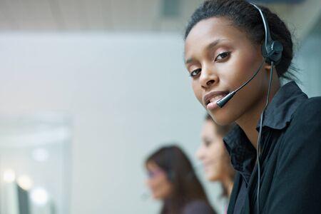 servicio al cliente: Grupo multi�tnica de representantes de servicio al cliente femenina hablando por tel�fono, con mujer africana mirando la c�mara. Copiar de forma horizontal, vista lateral, espacio Foto de archivo